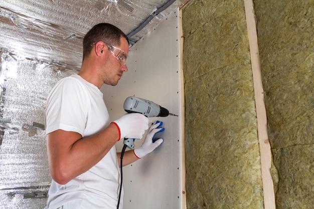 Pracownik w gogle ze śrubokrętem pracującym na izolacji. płyta gipsowo-kartonowa na belkach ściennych, izolująca wełna mineralna w drewnianej ramie. wygodny, ciepły dom, koncepcja ekonomiczna, budowlana i remontowa.