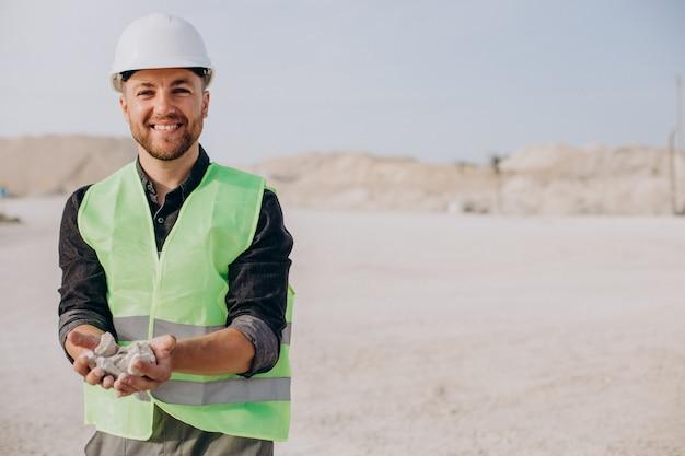 Pracownik w kamieniołomie piasku trzymający skały