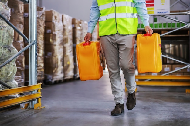 Pracownik w kamizelce przenosi puszki z olejem podczas chodzenia po magazynie.