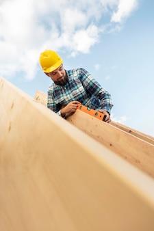 Pracownik w kasku i poziomicy sprawdzający belkę dachu domu