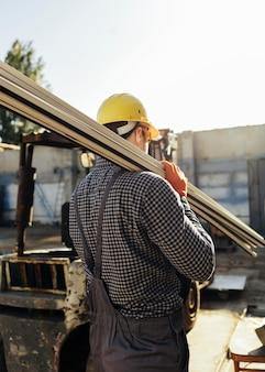 Pracownik w kasku niosącym drewno