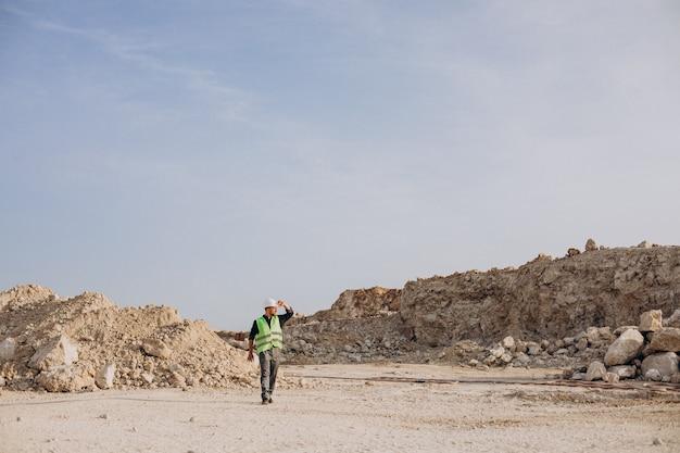 Pracownik w kasku stojący w kamieniołomie piasku