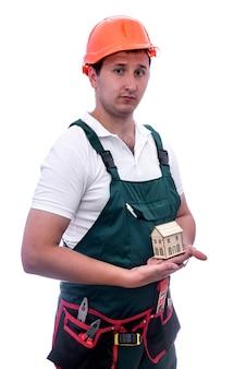 Pracownik w kasku trzymający drewniany model domu