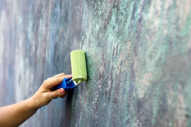 Pracownik w kombinezon malowanie ścian z rolką w kolorze zielonym z bliska