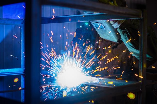 Pracownik w kombinezonie i masce ochronnej zgrzewa metal za pomocą spawarki