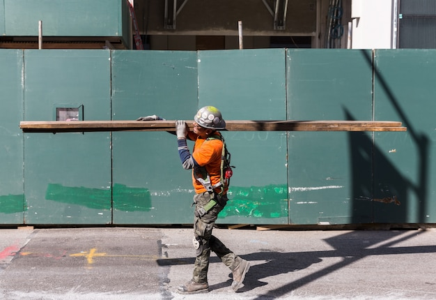 Pracownik w kombinezonie niesie deski na placu budowy