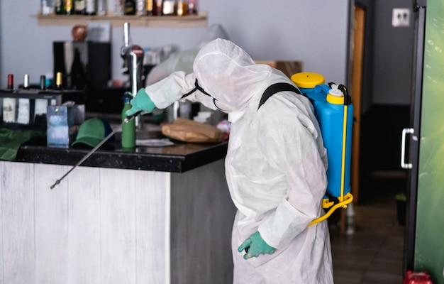 Pracownik w kombinezonie ochronnym noszącym maskę ochronną podczas dezynfekcji wewnątrz barowej restauracji