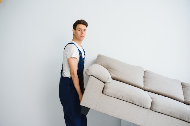 Pracownik w kombinezonie podnosi sofę