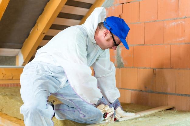 Pracownik w kombinezonie tnie materiał izolacyjny za pomocą rękawic i noża