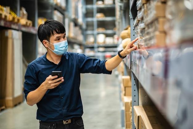 Pracownik w masce medycznej za pomocą smartfona do sprawdzania zapasów w magazynie podczas pandemii koronawirusa