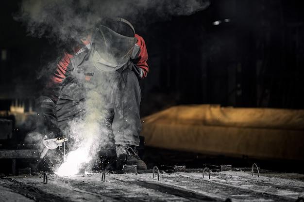 Pracownik w masce ochronnej zgrzewa metal za pomocą spawarki