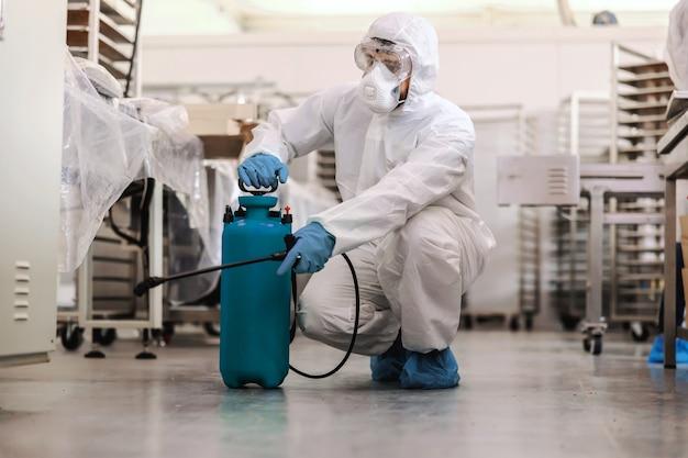 Pracownik w mundurze ochronnym z maską i gumowymi rękawiczkami kucający i spryskujący środkiem dezynfekującym w fabryce żywności. koncepcja wybuchu koronawirusa.