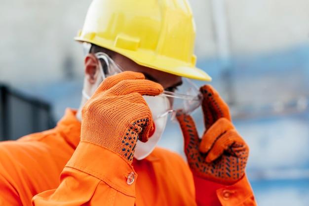 Pracownik w mundurze z kaskiem i okularami ochronnymi