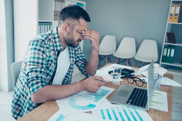 Pracownik w niebieskiej kraciastej koszuli pracuje w biurze