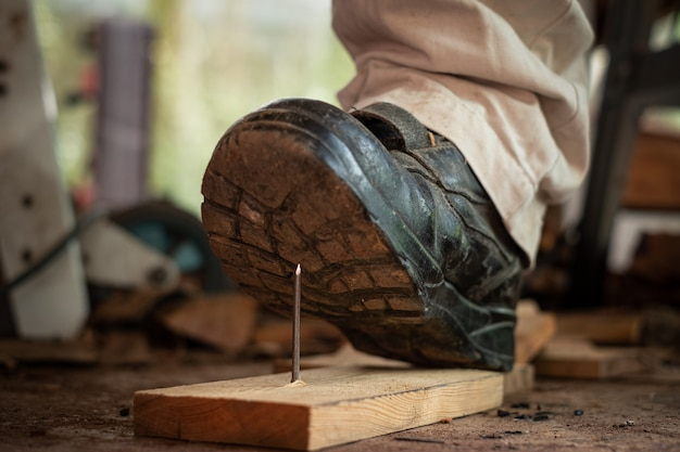 Pracownik w obuwiu ochronnym stąpający po gwoździach na desce na placu budowy