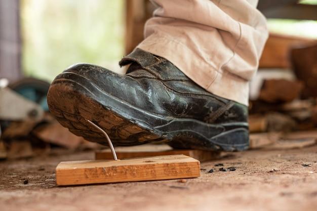 Pracownik w obuwiu ochronnym wchodzący na gwoździe na desce drewnianej w obszarze budowy