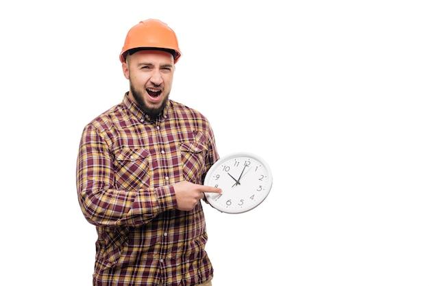 Pracownik w ochronnym hełmie trzymając budzik na białym tle. czas do pracy. czas budowy budynku
