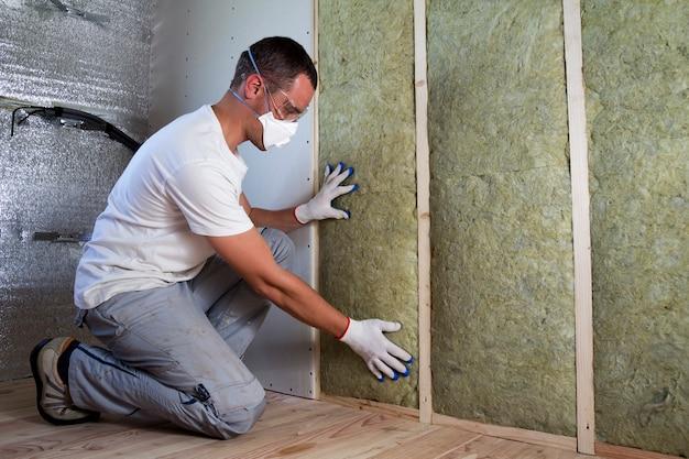 Pracownik w okularach ochronnych i masce izolacyjnej z wełny mineralnej do oddychania w drewnianej ramie na przyszłe ściany domu jako bariera zimna. wygodny, ciepły dom, ekonomia, konstrukcja i remont