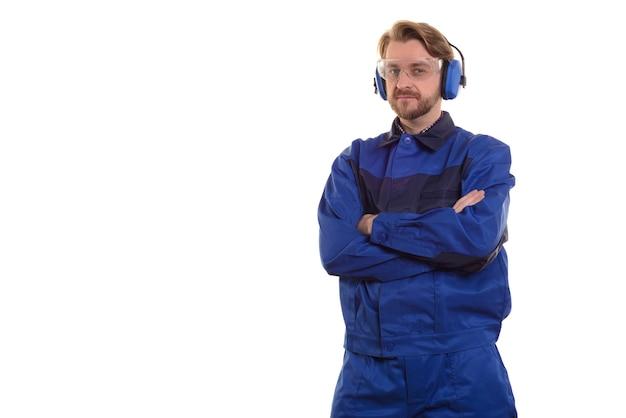 Pracownik w okularach ochronnych i słuchawkach stoi ze skrzyżowanymi rękami