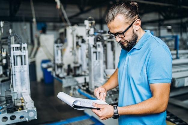 Pracownik w okularach stojący w pobliżu urządzeń przemysłowych i weryfikujący dane produkcyjne. mężczyzna gospodarstwa folderu w ręce