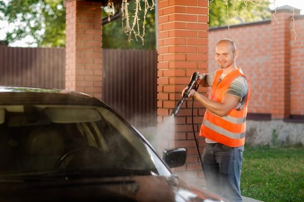 Pracownik w pomarańczowej kamizelce myje samochód.