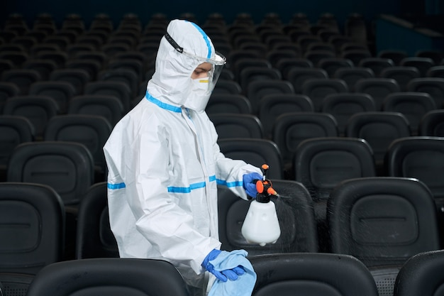 Pracownik w sali kinowej do czyszczenia odzieży ochronnej
