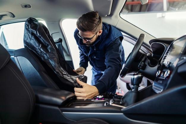 Pracownik w samochodzie próbuje założyć tapicerkę na fotelik samochodowy