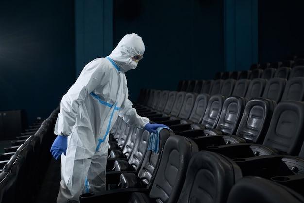 Pracownik w specjalnym garniturze wyciera szmatę z krzeseł w sali kinowej.