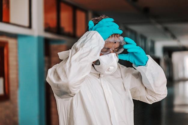 Pracownik w sterylnym białym mundurze, zdejmujący okulary, stojąc na korytarzu w szkole po dezynfekcji.