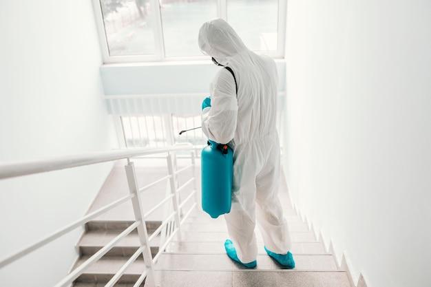 Pracownik w sterylnym mundurze, w rękawiczkach i masce do sterylizacji balustrady w szkole.