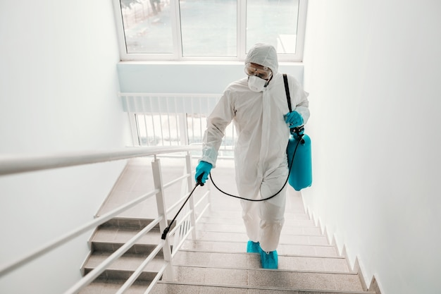 Pracownik w sterylnym mundurze, w rękawiczkach i masce do sterylizacji poręczy w szkole.