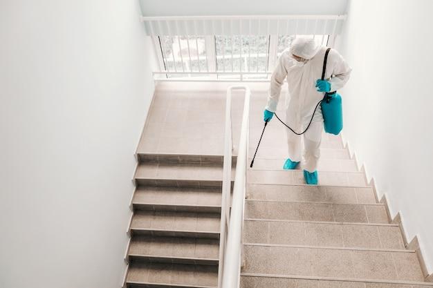 Pracownik w sterylnym mundurze, w rękawiczkach i masce do sterylizacji schodów w szkole.