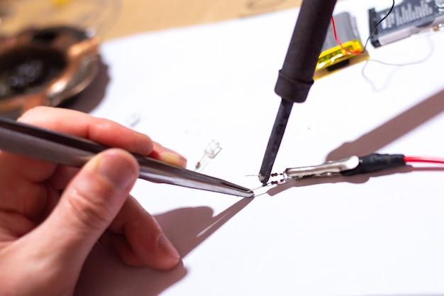 Pracownik w warsztacie lutujący diodę elektryczną