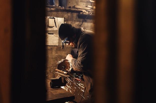 Pracownik w warsztacie wycina metalowy kawałek szlifierki.