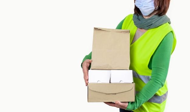 Pracownik w zielonej kamizelce trzyma dużo pudełek papierowych, koncepcja dostawy.