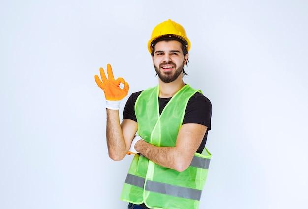 Pracownik w żółtym kasku i rękawice warsztatowe pokazujący znak przyjemności.