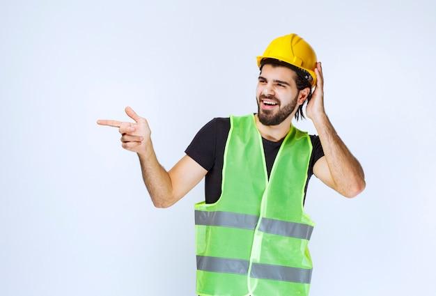 Pracownik w żółtym kasku myśli i wygląda na zdezorientowanego.