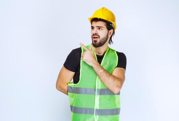 Pracownik w żółtym kasku pokazujący lewą stronę.