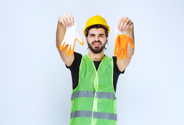 Pracownik w żółtym kasku wyjmując i demonstrując swoje rękawice warsztatowe.