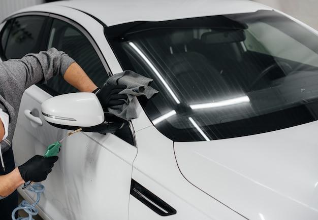 Pracownik wieje i wyciera samochód po umyciu. myjnia samochodowa.