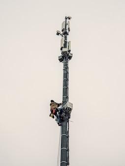 Pracownik wieżowca pracuje na wieży komórkowej.
