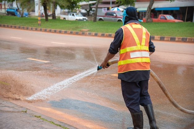 Pracownik wodny cleaning po ulicznego rynku.