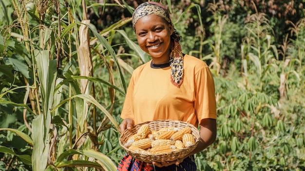 Pracownik wsi pozuje z kukurydzą