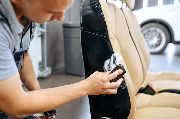 Pracownik wyciera fotel samochodowy, pranie chemiczne i detale