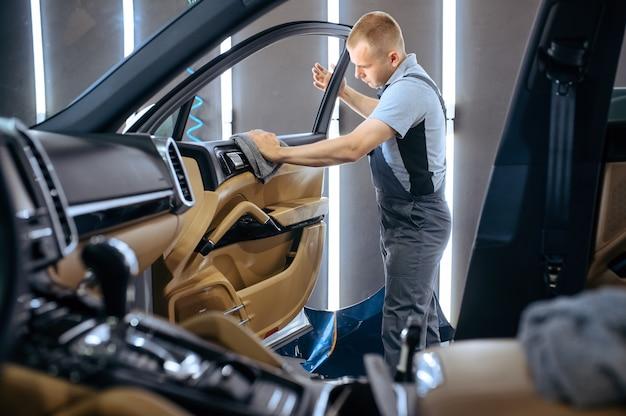 Pracownik wyciera szmatką tapicerkę drzwi samochodu, czyści chemicznie i detaluje