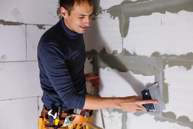 Pracownik wyciera szwy na zewnątrz murowanego domu. budowniczy przetwarza mur. murarz budowlany pracownik murarz instalacji czerwonej cegły z szpachlą szpachlową na zewnątrz.
