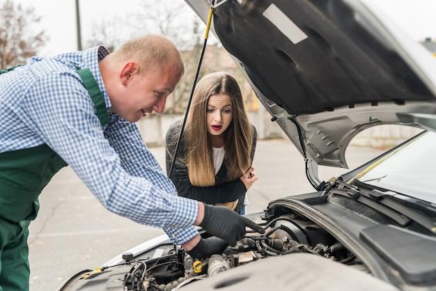 Pracownik wyjaśnia kobiecie problem w silniku