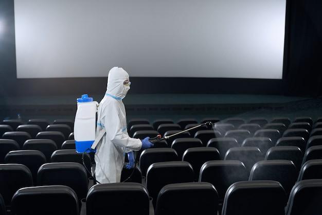Pracownik wykonujący dezynfekcję specjalnym sprzętem w kinie.