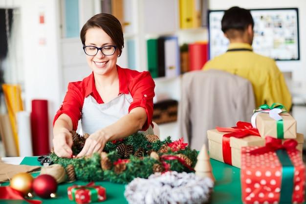 Pracownik wykonujący wieniec świąteczny i pakujący pudełka na prezenty