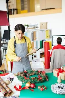 Pracownik wykonujący wieniec świąteczny